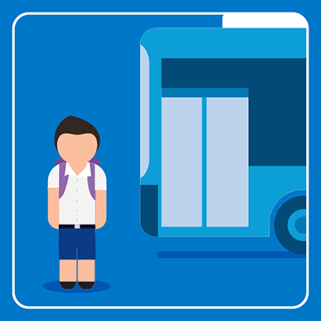 School student is standing next to a bus waiting for it to come to a stop.